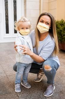 Vista frontale della madre e del bambino con maschere mediche