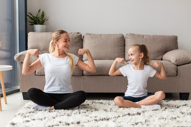 Front view of mother and daughter at home showing off biceps