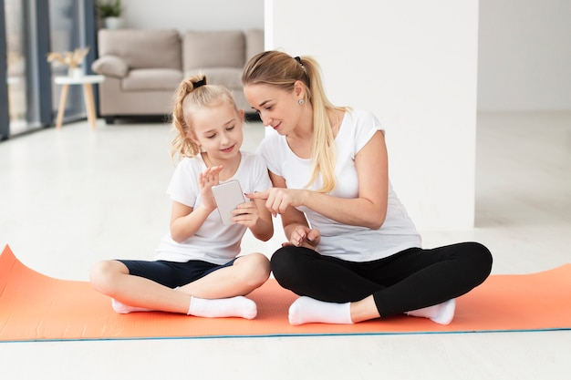 Front view of mother and daughter at home on yoga mat playing on smartphone