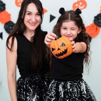 Front view of mother and daughter with pumpkin