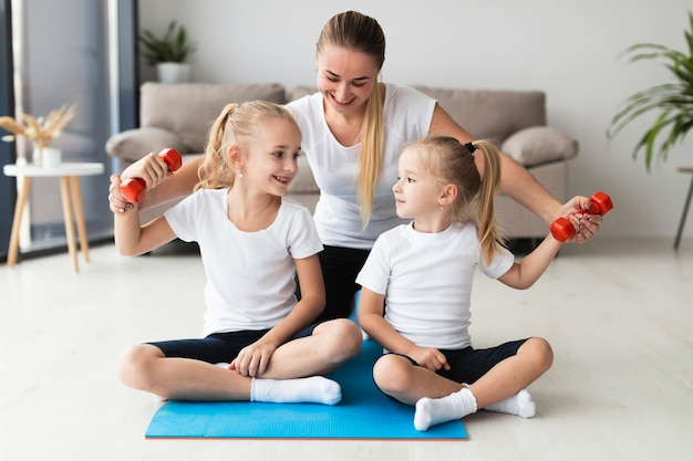 Front view of mother and daughters exercising at home