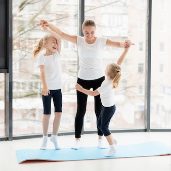 Front view of mother and daughters working out at home