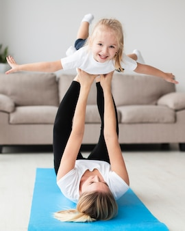 Front view of mother exercising with happy child at home