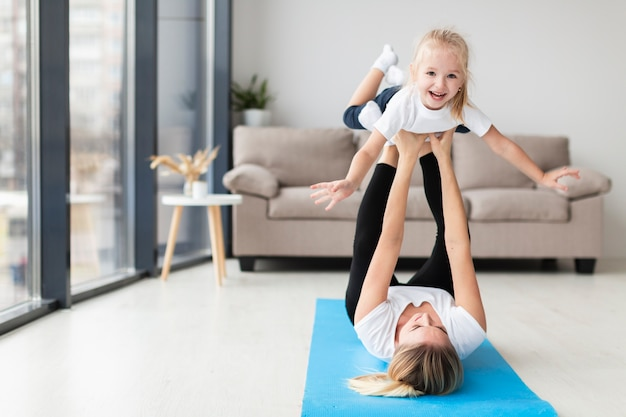Front view of mother exercising with smiley child at home