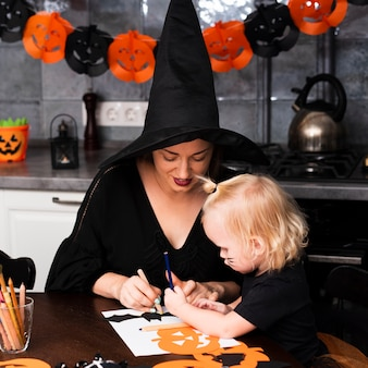 Front view of mother and kid with halloween elements