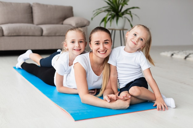 Front view of mother posing with daughters on yoga mat at home