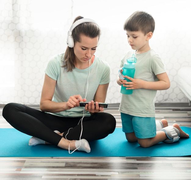 Front view mother together with son on yoga mat
