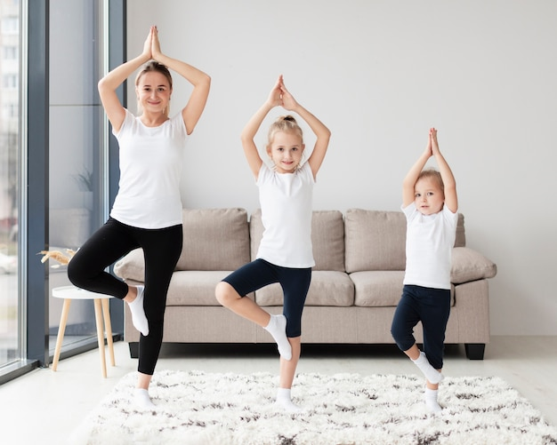 Front view of mother with daughters at home exercising
