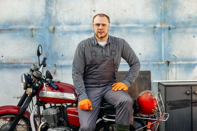 Vista frontale del meccanico del motociclo con guanti e occhiali protettivi