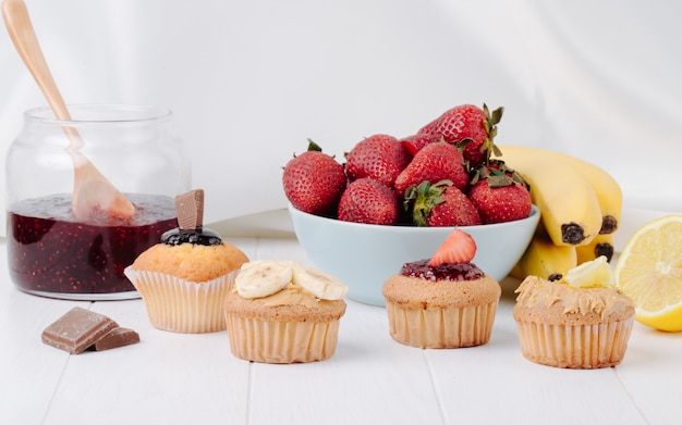 Front view muffins with bananas strawberries chocolate and lemon on a white surface