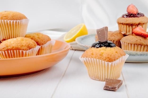 Вид спереди кексы с шоколадом и клубникой на тарелку с лимоном