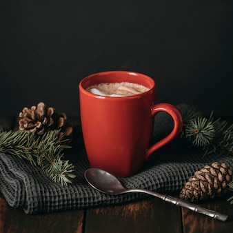 Front view mug with hot chocolate and pine cones