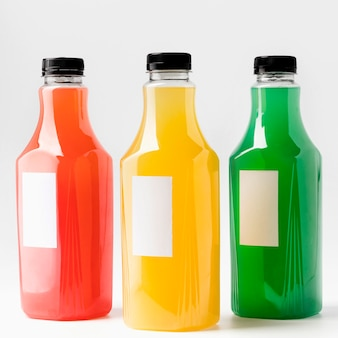 Front view of multicolored juice bottles with caps