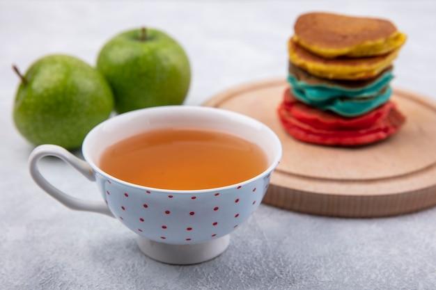 Разноцветные блины на подставке с зелеными яблоками и чашкой чая на белом фоне вид спереди