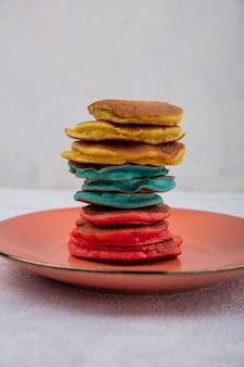 正面図白い背景の上のオレンジ色のプレートに色とりどりのパンケーキ