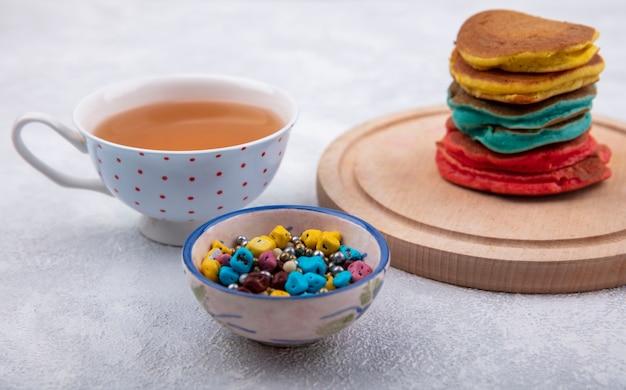 Vista frontale frittelle multicolori su un supporto con cioccolatini colorati e una tazza di tè su uno sfondo bianco
