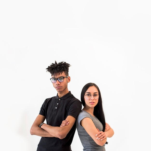 Front view of multiethnic man and woman looking at camera standing against white backdrop