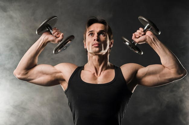 Front view of muscled man lifting weights