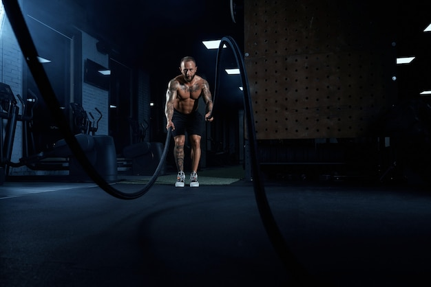Front view of muscular brunette man doing battle rope training in gym in dark atmosphere.