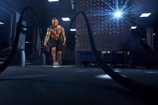 Front view of muscular brunette shirtless man doing battle rope training in gym in dark atmosphere.