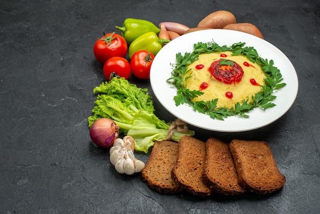 Piatto di purè di patate vista frontale con pagnotte di pane scuro e verdure su spazio scuro