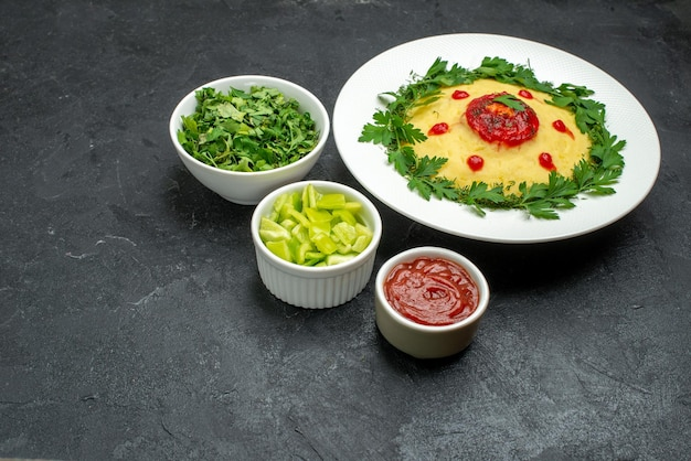 Вид спереди картофельное пюре с томатным соусом и зеленью на темном пространстве
