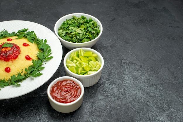 暗い空間にトマトソースと緑のマッシュポテトの正面図