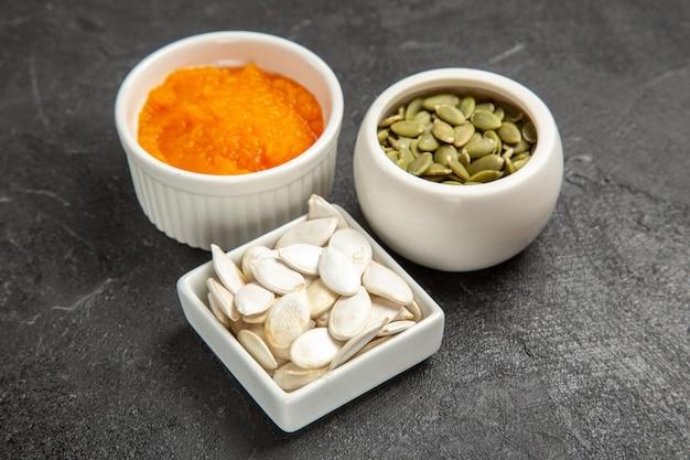 正面図濃い灰色の背景色の種子熟したオレンジ色の写真に種子とカボチャをつぶ