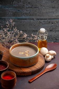 Zuppa di funghi vista frontale con diversi condimenti nello spazio buio