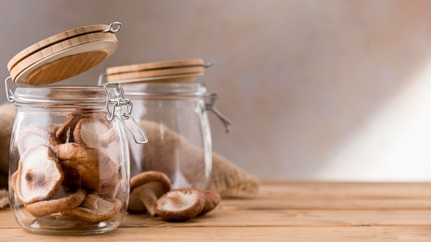 Front view of mushrooms in clear jars with copy space