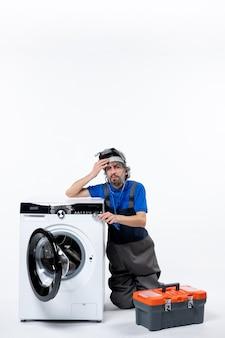 Vista frontale del riparatore meditabondo seduto vicino alla borsa degli attrezzi della lavatrice sul muro bianco