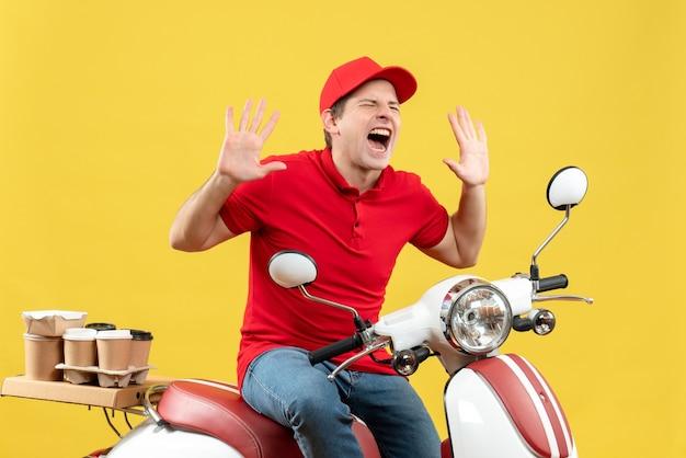 Vista frontale del giovane ragazzo arrabbiato nervoso che indossa la camicetta rossa e il cappello che trasporta gli ordini che indicano su su fondo giallo