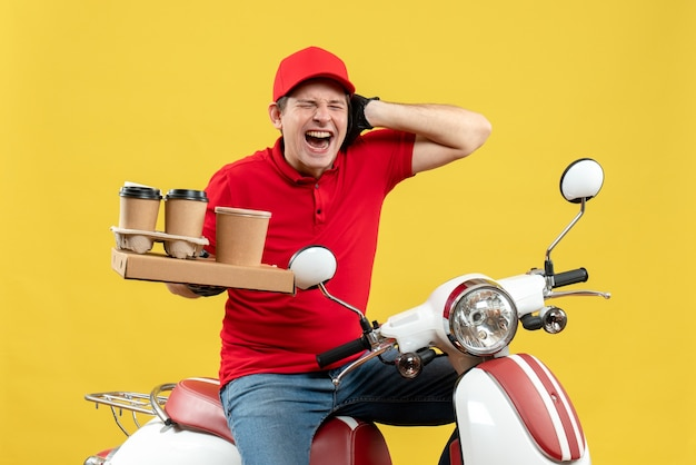 Vista frontale del corriere nervoso uomo che indossa camicetta rossa e guanti cappello in maschera medica consegna ordine seduto su scooter tenendo ordini chiudendo il suo orecchio