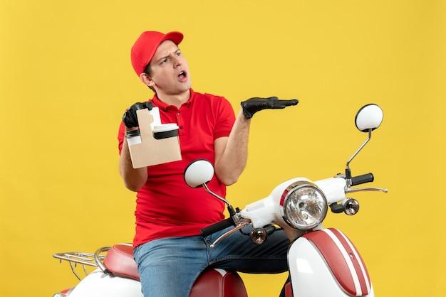 Vista frontale del corriere nervoso uomo che indossa camicetta rossa e guanti cappello in maschera medica consegna ordine seduto su scooter tenendo gli ordini indicando qualcosa sul lato sinistro