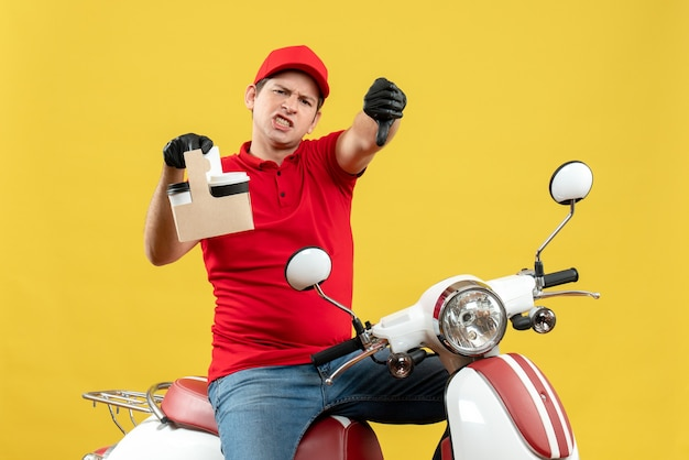 Vista frontale del corriere nervoso uomo che indossa camicetta rossa e guanti cappello in maschera medica consegna ordine seduto su scooter tenendo gli ordini con il pollice verso il basso