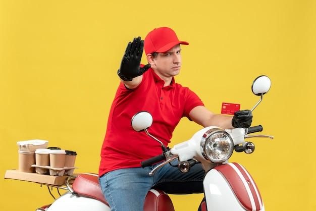 Vista frontale dell'uomo nervoso del corriere che indossa guanti rossi della camicetta e del cappello nella mascherina medica che consegna l'ordine che si siede sullo scooter che mostra la carta di credito