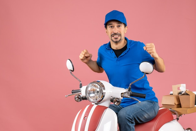 Front view of nervous delivery guy wearing hat sitting on scooter on pastel peach background