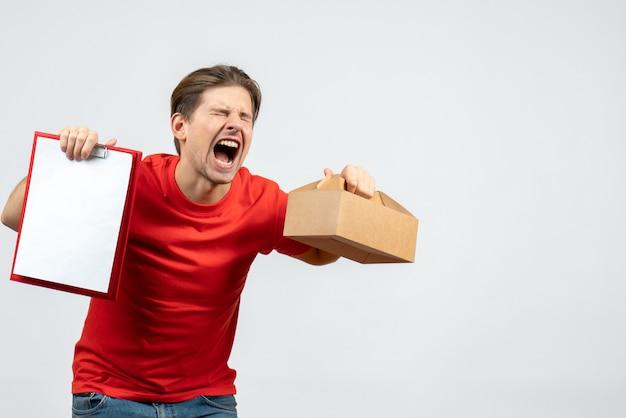 Vista frontale del giovane emotivo nervoso in camicia rossa che tiene scatola e documento su priorità bassa bianca