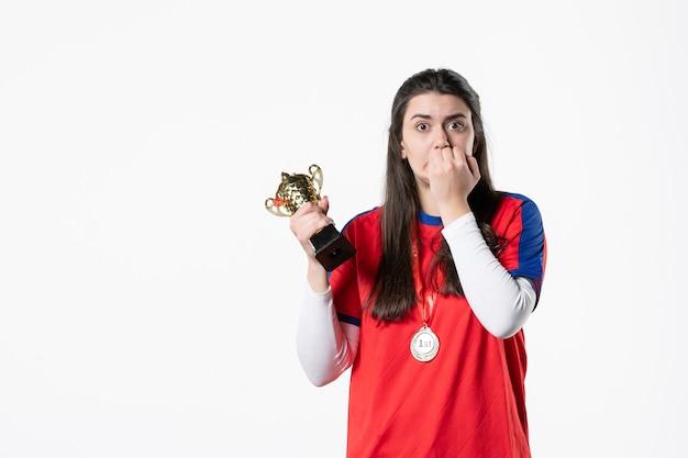 Вид спереди нервная женщина-игрок с золотым кубком и медалью