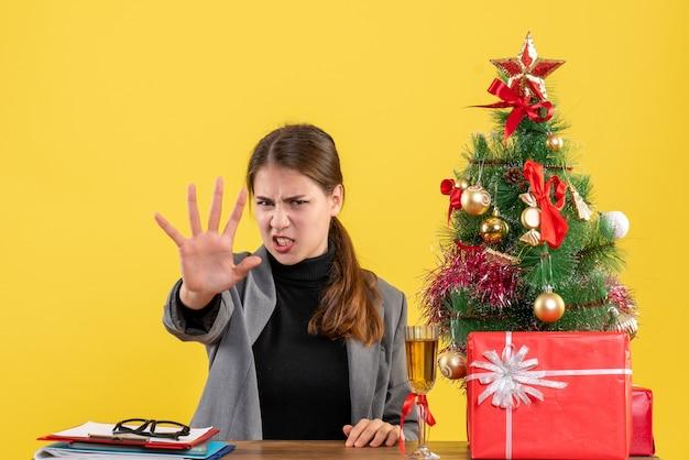Вид спереди нервная девушка, сидящая за столом, делая жест остановки возле рождественской елки и подарочного коктейля