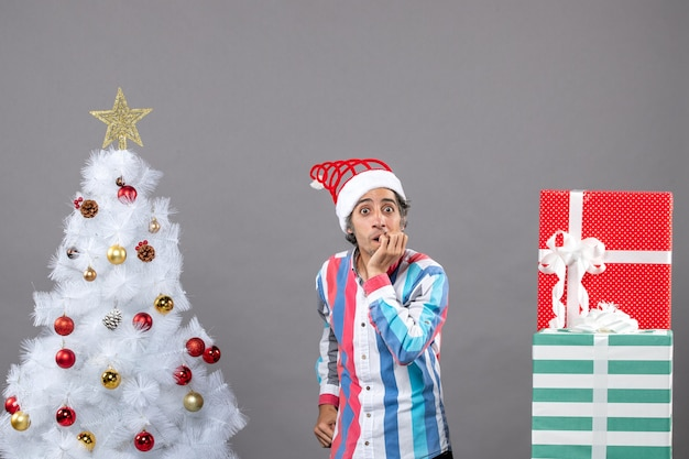 흰색 크리스마스 트리 근처 그의 마우스에 손을 넣어 전면보기 긴장 남자