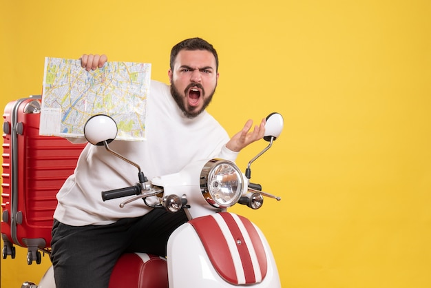 Front view of nervous man sitting on motorcycle with suitcase on it holding map on isolated yellow background