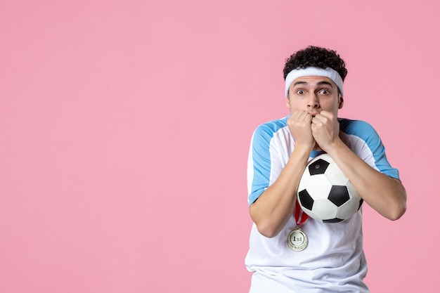 Вид спереди нервного футболиста в спортивной одежде с мячом