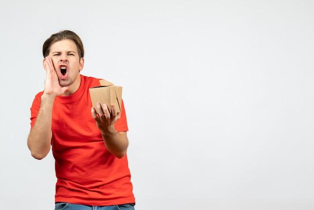 Vista frontale del giovane ragazzo nervoso in camicetta rossa che tiene piccola scatola che chiama qualcuno su priorità bassa bianca