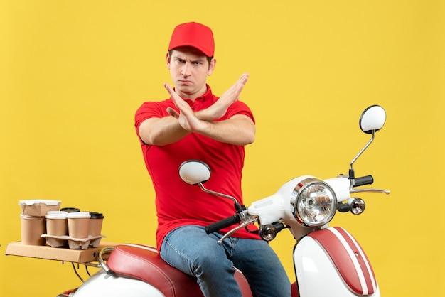 Vista frontale del giovane ragazzo nervoso che indossa la camicia rossa e il cappello che consegna gli ordini che fanno il gesto di arresto su fondo giallo
