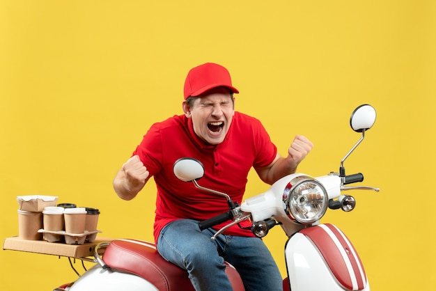 Front view of nervous young guy wearing red blouse and hat delivering orders on yellow background