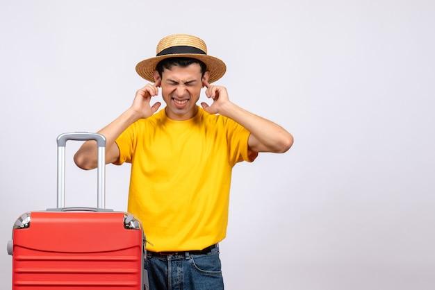 黄色のtシャツと耳を保持している麦わら帽子と正面図神経質な若い男