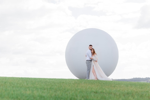 Front view of newlyweds in love stand on the background of a white monument in the shape of a ball in the middle of the field