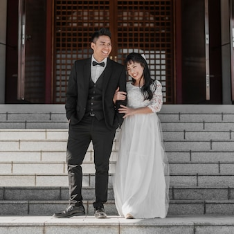 Front view of newlyweds posing together on steps