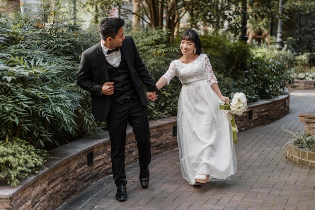 Front view of newlyweds walking down the street